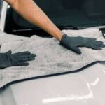 144554869-car-detailing-wash-and-cleaning-concept-cropped-image-of-hands-of-male-professional-car-wash-worker-